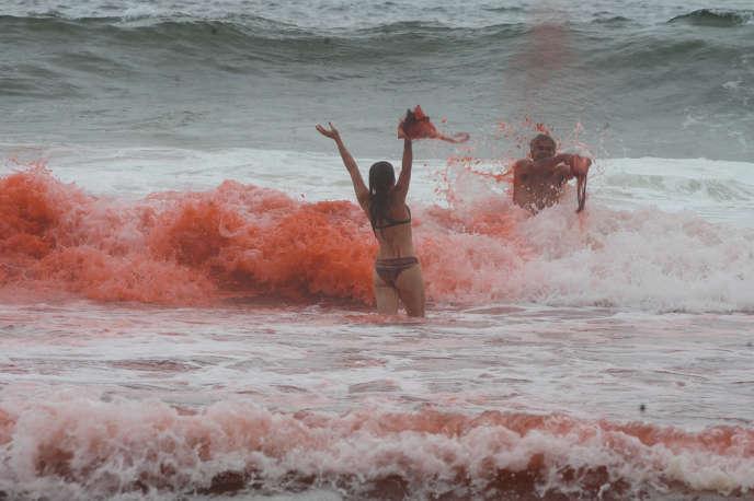 30 novembre 2013, Rio de Janeiro: l'artiste Ronald Duarte teinte la mer de poudre de betterave pour dénoncer les violences policières.