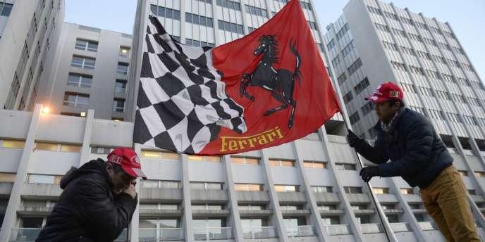 Deux supporteurs de Michael Schumacher avec un drapeau Ferrari, le 31 décembre devant le CHU de Grenoble.