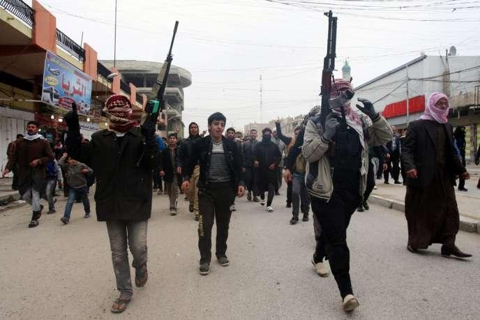 Des combattants sunnites chantent des slogans hostiles au gouvernement du premier ministre chiite Nouri Al-Maliki lors des funérailles d'un homme tué dans des combats entre Al-Qaida et l'armée irakienne, le 4 janvier, à Fallouja, en Irak.