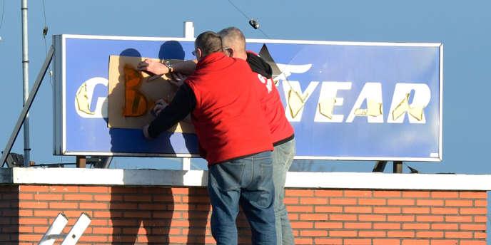 Les employés de l'entreprise Goodyear transforme le signe de l'usine en