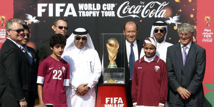 Des officiels de la FIFA présentent le trophée de la Coupe du monde, le 12 décembre 2013 à Doha.