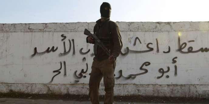 Un combattant de l'Armée syrienne libre pose devant un graffiti «A bas Da'ech» («l'Etat islamique en Irak et au Levant», djihadiste), le 7janvier à Alep.