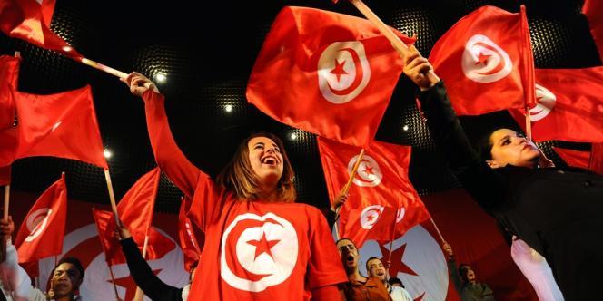Des Tunisiens brandissent le drapeau national lors du troisième anniversaire de la fuite de l'ancien président Zinedine El-Abidine Ben Ali, le 14 janvier 2014 sur l'avenue Habib-Bourguiba, à Tunis.