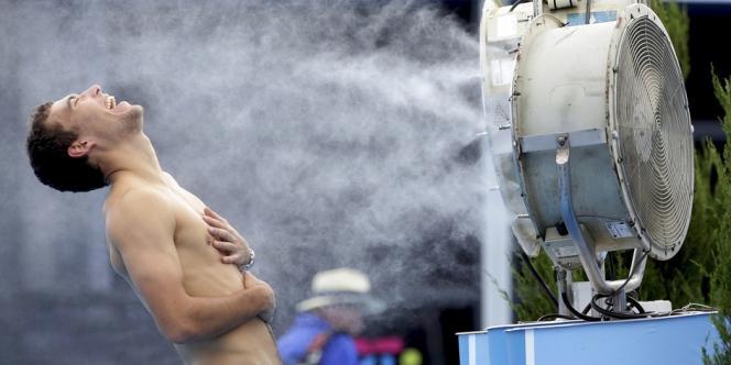 Le joueur de tennis polonais Jerzy Janowicz se rafraichit lors de l'Open d'Australie, le jeudi 16 janvier à Melbourne.