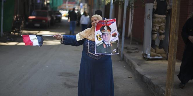 Une femme tient le portrait du général Al-Sissi, mercredi 15 janvier au Caire.