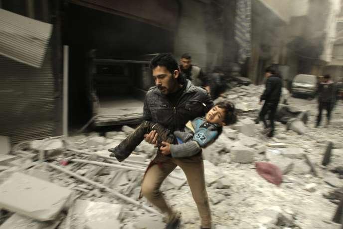 Cet enfant qui a survécu a un raid aérien de l'armée syrienne est transporté par un rebelle, dans une rue d'Alep, le 21 janvier.