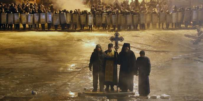 Des prêtres orthodoxes se tiennent entre les forces de l'ordre ukrainiennes et les manifestants, le 24 janvier, à Kiev.