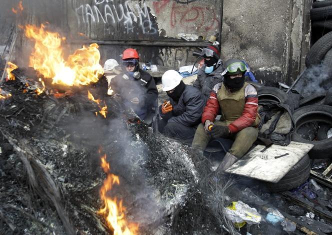 Une scène devenue banale dans le centre-ville de Kiev : des protestataires se reposent derrière les barricades de la rue Hrousevskoho, mardi 28 janvier.