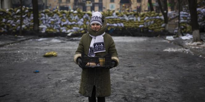 Une militante distribue de la nourriture aux protestataires qui tiennent les barricades de Maïdan, à Kiev, mardi 28 janvier.