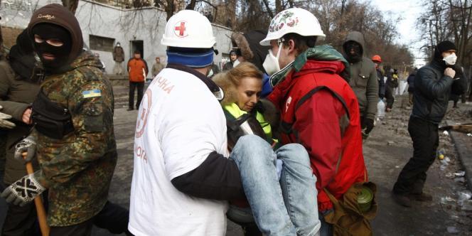 Des secouristes volontaires transportées une blessée dans des heurts avec les forces de l'ordre, lundi 20 janvier à Kiev.