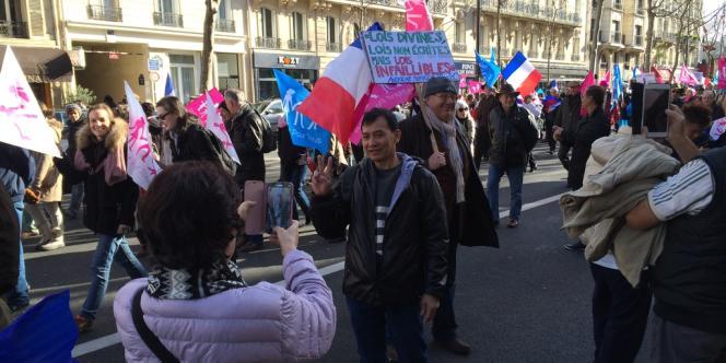 Des touristes se prennent en photo devant le défilé de la Manif pour tous du 2 février à Paris. Un manifestant leur dit :