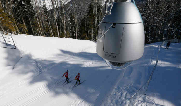 Unidentified cross country skiers pass by a security camera as a security guard watches them as they train prior to the 2014 Winter Olympics, Tuesday, Feb. 4, 2014, in Krasnaya Polyana, Russia. (AP Photo/Dmitry Lovetsky)