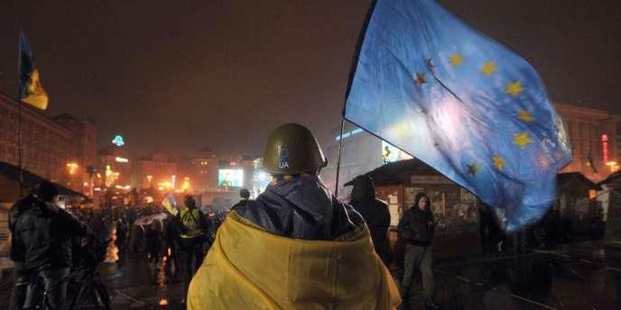 Un militant ukrainien pro-européen brandissant un drapeau de l'UE, sur la place de l'Indépendance à Kiev, en janvier 2014 .