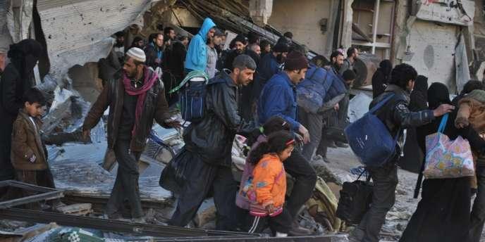 Des familles de Homs quittent le centre de la ville, assiégé par l'armée syrienne depuis plus de vingt mois, le 12 février 2014.