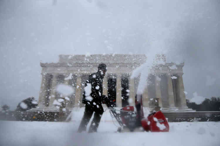 A Park Service employee clears snow in front of the Lincoln Memorial in Washington, Thursday, Feb. 13, 2014. After pummeling wide swaths of the South, a winter storm dumped nearly a foot of snow in Washington as it marched Northeast and threatened more power outages, traffic headaches and widespread closures for millions of residents. (AP Photo/Charles Dharapak)