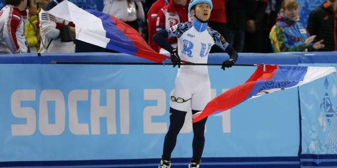 Le Russe Victor An fête sa victoire, drapeaux en main, aux JO 2014 de Russie.