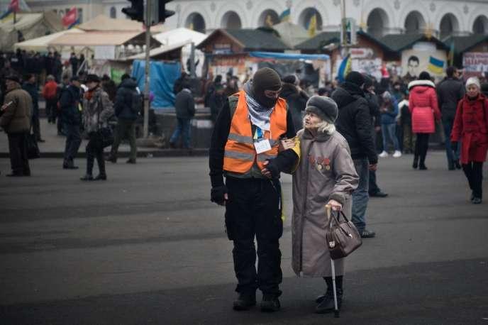 Un militant opposé au gouvernement parle à une vieille dame à Maïdan, à Kiev, le 15février.