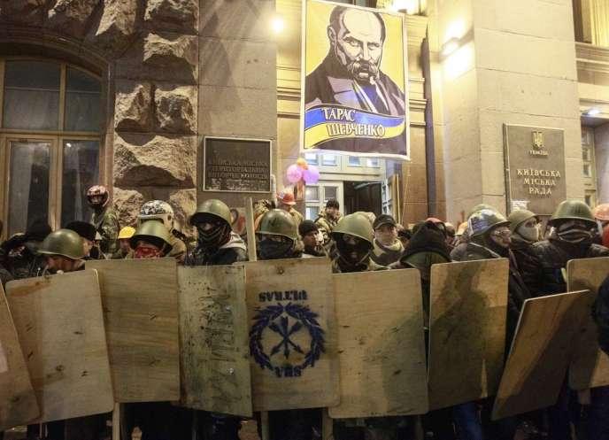 Des manifestants antigouvernementaux évacuent  la mairie de Kiev, dimanche 16 février.