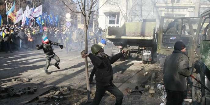 Des manifestants lancent des projectiles sur les forces de l'ordre rassemblées devant le Parlement ukrainien, à Kiev, le 18 février.