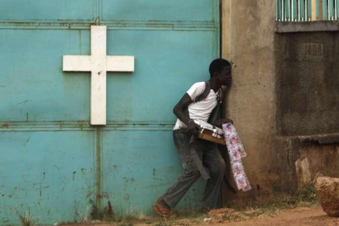 Un vendeur de rue se protège derrière une église, le 18 février, lors d'échanges de tirs entre forces militaires africaines et membres de la milice anti-balaka, à Bangui.
