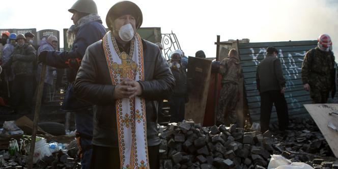Un prêtre orthodoxe près des barricades érigées par les manifestants pour se protéger des affrontements avec les forces de l'ordre.