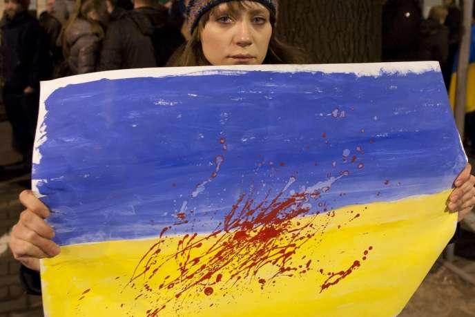 Une femme brandit une peinture figurant un drapeau ukrainien tâché de sang, devant l'ambassade d'Ukraine en Pologne, le 20 février.