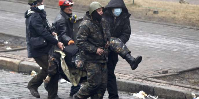 Evacuation d'un blessé par des opposants sur Maïdan, jeudi 20 février.
