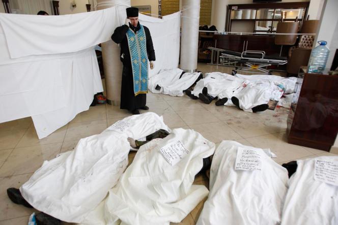 Dans un hôtel à Kiev, un prêtre parle au téléphone près des corps de plusieurs manifestants tués par les forces de l'ordre ukrainiennes.