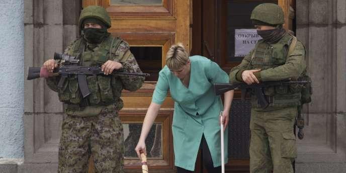 Deux soldats sans insignes, probablement russes, gardent l'entrée du siège du gouvernement local de Simferopol, en Crimée, le 2 mars.
