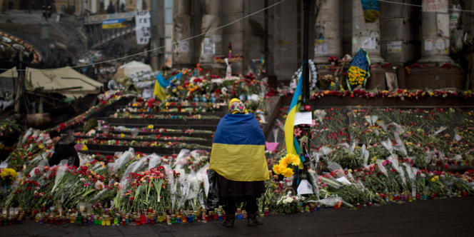 A woman wearing a Ukrainian flag stands at a memorial for people killed in clashes with the police at Kiev's Independence Square, Ukraine, Monday, March 3, 2014. The U.S. and its allies are weighing sanctions on Moscow and whether to bolster defenses in Europe in response to Russia's military advances on Ukraine. (AP Photo/Emilio Morenatti)