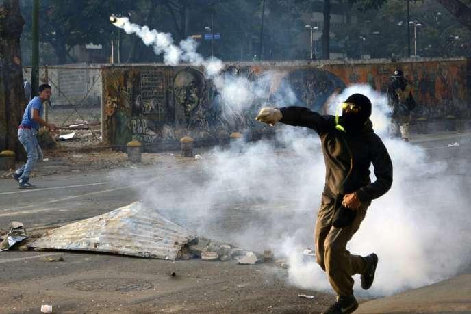 Un manifestant renvoie une grenade lacrymogène lancée par la police, mercredi 5 mars 2014, à Caracas, au Venezuela.