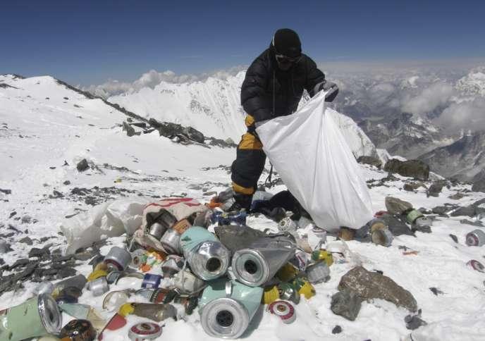 Un sherpa népalais ramasse des détritus laissés par les alpinistes, sur le Mont Everest, à 8 000 mètres d'altitude.