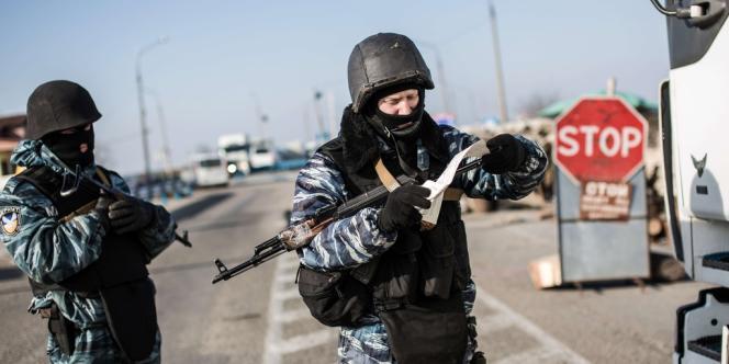 Un homme armée, prorusse, contrôle des papiers à un barrage filtrant à l'entrée de la Crimée, à Chongar, lundi10mars.