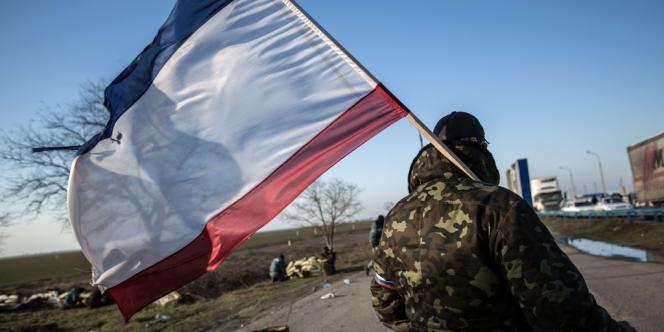 Un militant prorusse porte un drapeau de la Crimée au point de contrôle de Chongar bloquant l'entrée en Crimée, le 10mars.