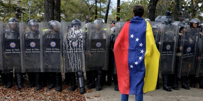 Un étudiant se tient devant la police, le 12 mars à Caracas.