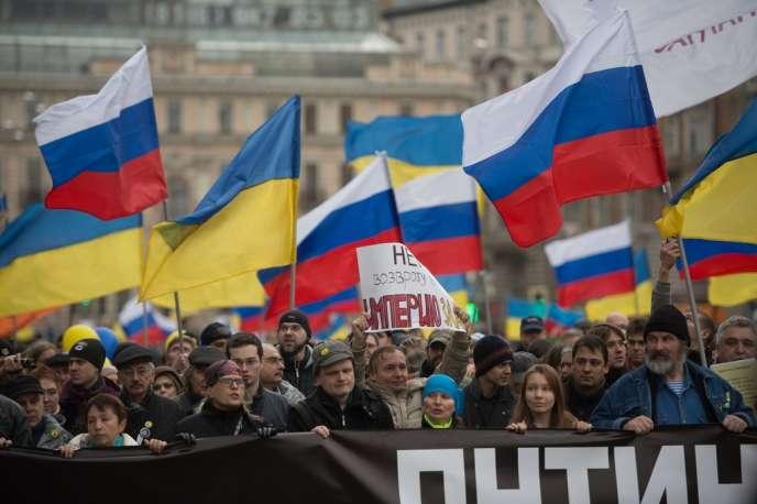 Des manifestants portant les drapeaux de la Russie et de l'Ukraine rassemblés contre la politique russe en Crimée, le 15 mars 2014, à Moscou.