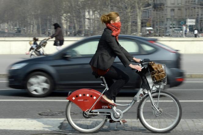 Cycliste se protégeant de la pollution sur un Velov, à Lyon, vendredi 14 mars.