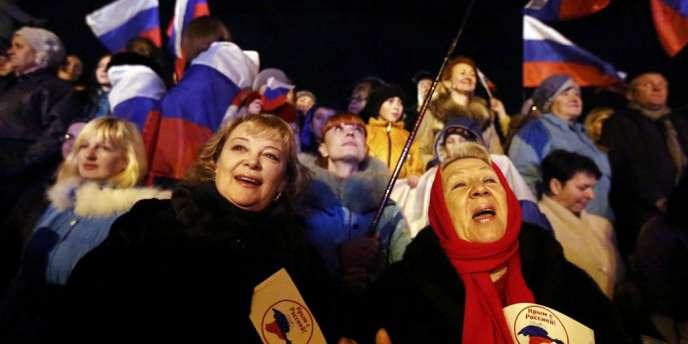 Des Criméens suivent l'annonce des résultats du référendum sur un rattachement de la péninsule à la Russie, le16mars.