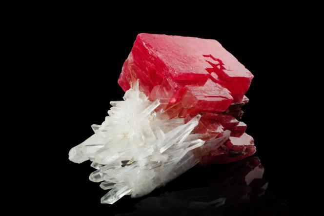 Rhodochrosite en rhomboèdre sur cristaux de quartz blanc de 14 cm de long.