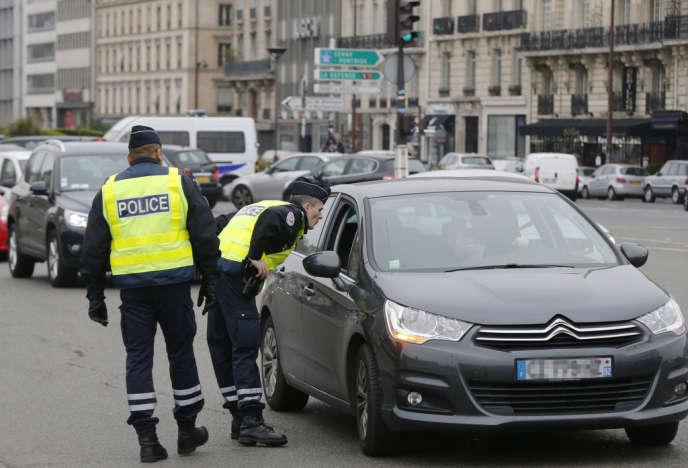 Des policiers contrôlent un véhicule à Paris, lundi 17 mars. Une mesure de circulation alternée a été mise en place dans la capitale et 22 communes de la petite couronne.