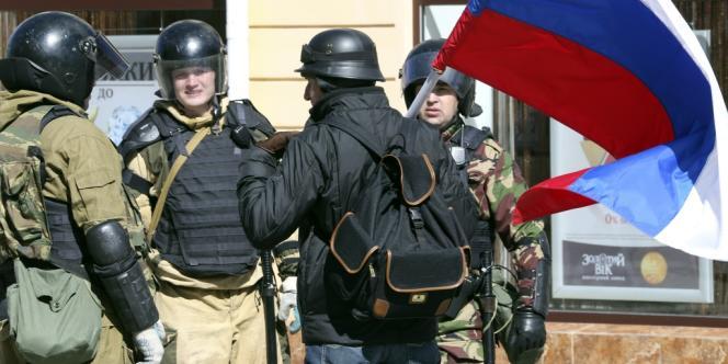Des hommes armés discutent avec un homme portant le drapeau russe, le 17 mars à Simféropol, en Crimée.