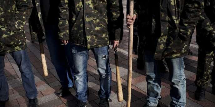 Des volontaires ukrainiens devant le Parlement à Kiev, lundi 17 mars.
