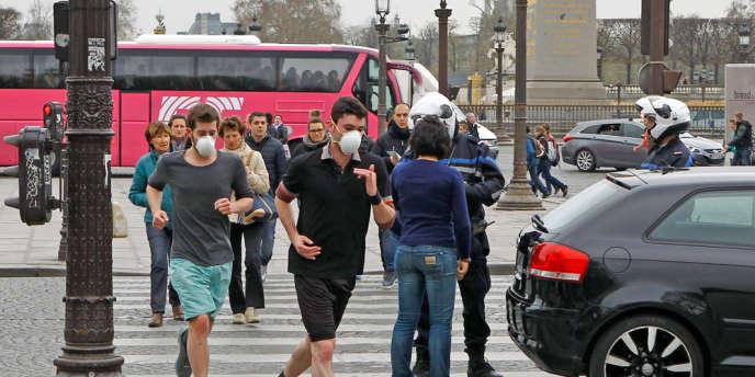 Des joggers courent dans une rue de Paris, en essayant de se protéger de la pollution. Au second plan, la police contrôle la circulation, réglementée dans la capitale et dans ses communes limitrophes, le 17 mars