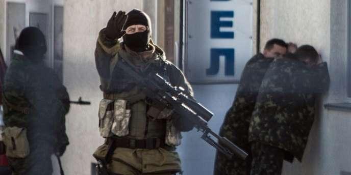 Arrestation d'officiers ukrainiens par des hommes armés russes à Simferopol, mardi.