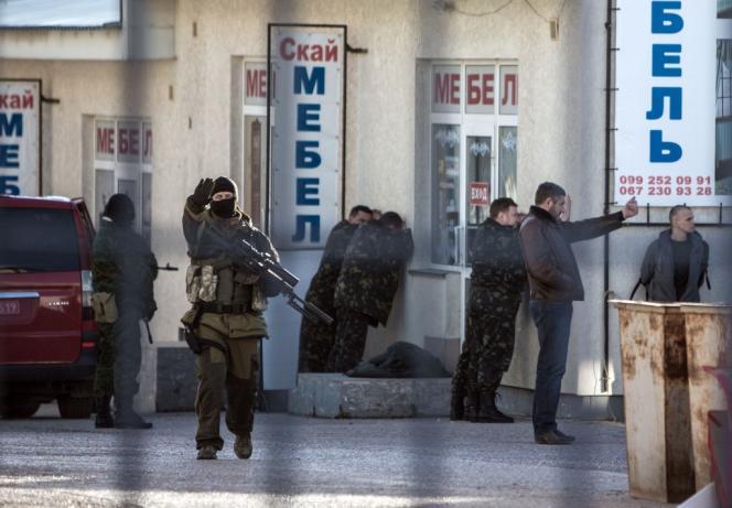 Des soldats russes capturent des militaires ukrainiens à Simferopol, le 18 mars.