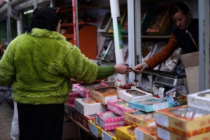 Une femme paie en hryvnia, la monnaie ukrainienne, mardi 18 mars sur un marché de Simferopol.