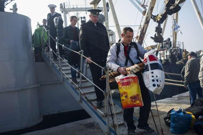 Des marins et officiers ukrainiens quittent la corvette «Khmelnitsky», saisie par les forces prorusses, jeudi 20 mars, à Sébastopol.