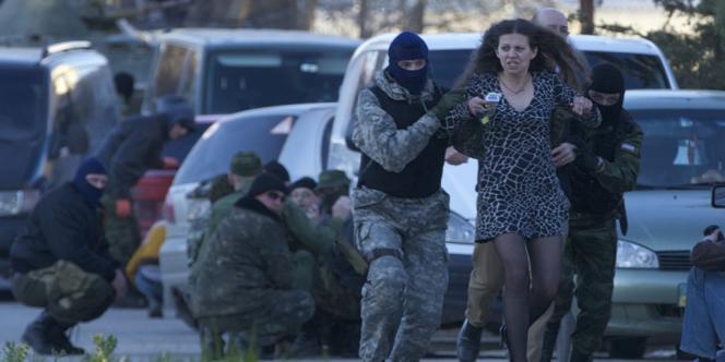 Des membres de milices pro-russes évacuent des résidents locaux lors de l'assaut des troupes russes contre la base aérienne de Belbek en Crimée, le 22 mars.
