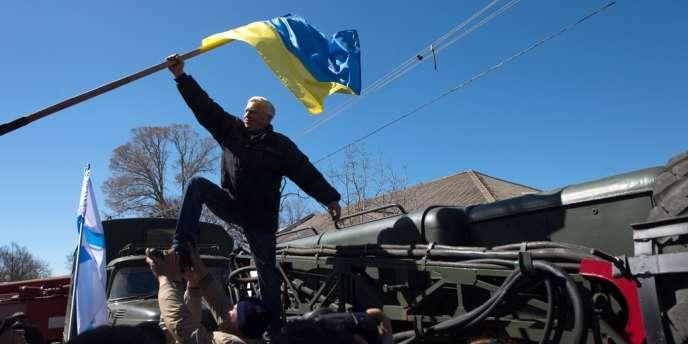 Des manifestants prorusses retirent le drapeau ukrainien de la base aérienne de Novofedorivka, en Crimée, le 22 mars.