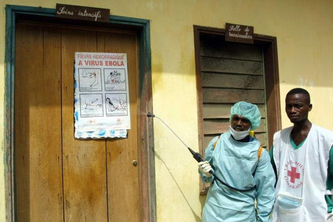 Deux membres de la Croix-Rouge désinfectent à l'aide d'un spray la salle de soins intensifs de l'hopital de Kellé au Congo, en 2003.